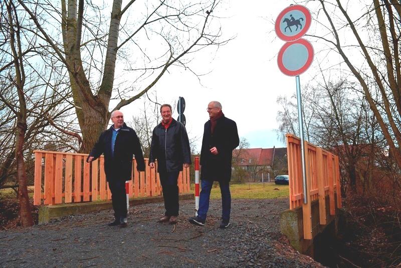 Edmund Galli, Jürgen Müller und Bürgermeister Gerald Frank (von links) testen bei einem Spaziergang über die Semme erfolgreich die frisch renovierte Brücke, die jetzt wieder für Fußgänger freigegeben ist.