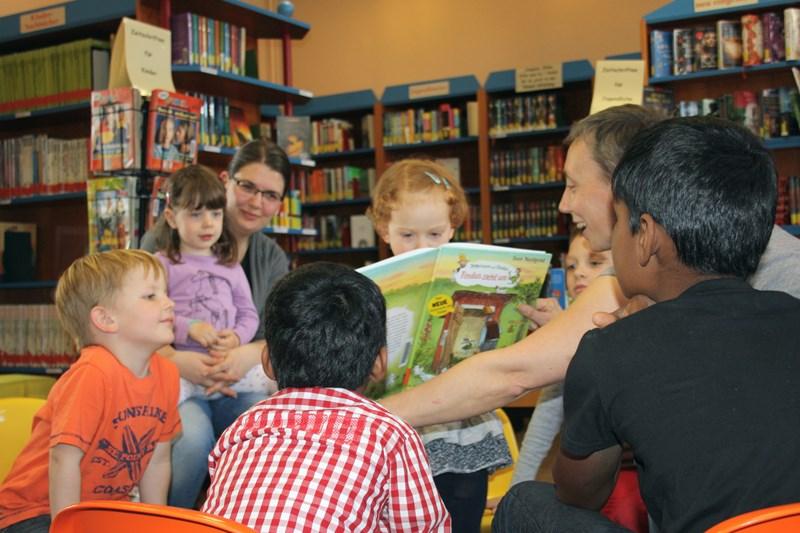 """Das Foto zeigt Bücherei-Mitarbeiterin Anja Christ, die Kindern aus """"Findus zieht um"""" vorliest."""