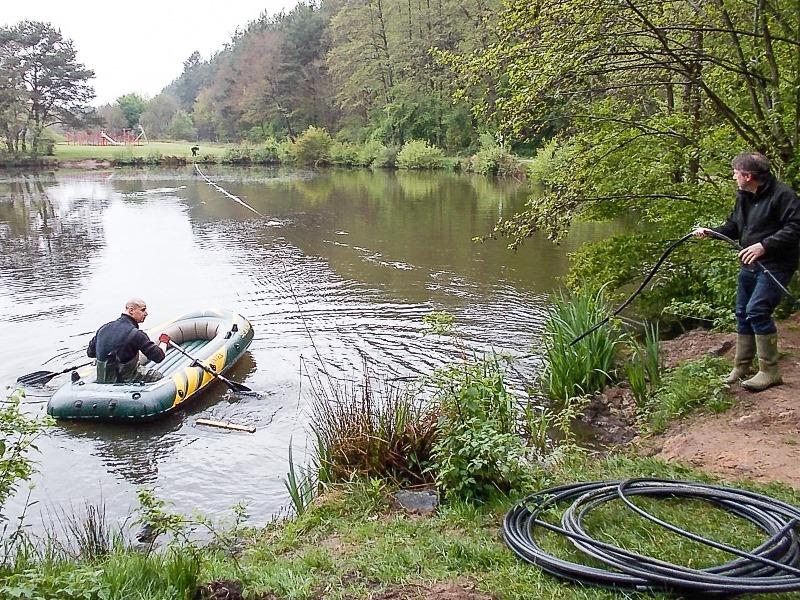 Mitarbeiter der Firma Drausy bringen die Schläuche im Teich des Freizeitzentrums aus.