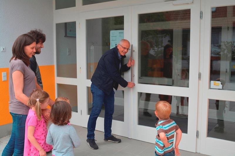 Bürgermeister Gerald Frank öffnet die Pforten der frisch renovierten Kita Im Rüssel für die Elternbeiräte Alexander Haus und Corinna Thom und deren Kinder. Bald ziehen Erzieher und Kinder hier ein.