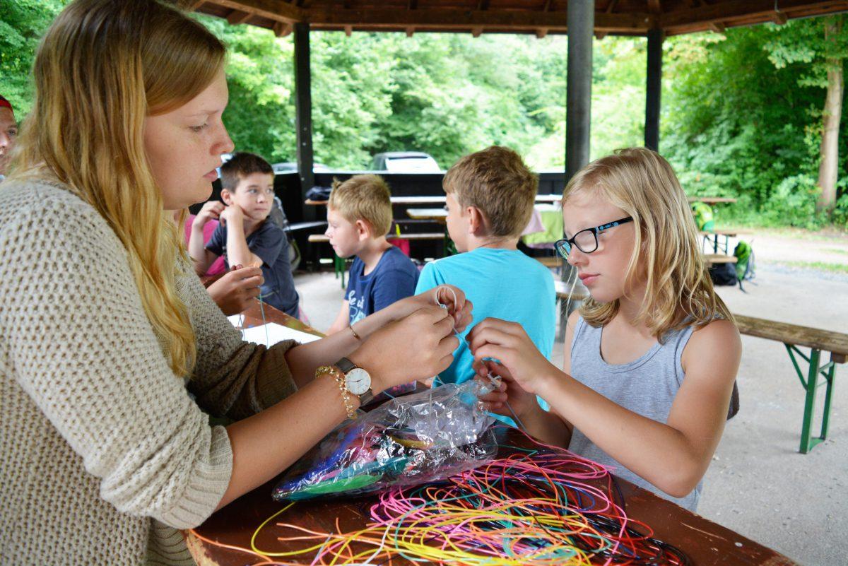 BU: Betreuerin Patrizia Friedrich zeigt den Kindern, wie man aus den bunten Plastikfäden schöne Armbänder knoten kann.