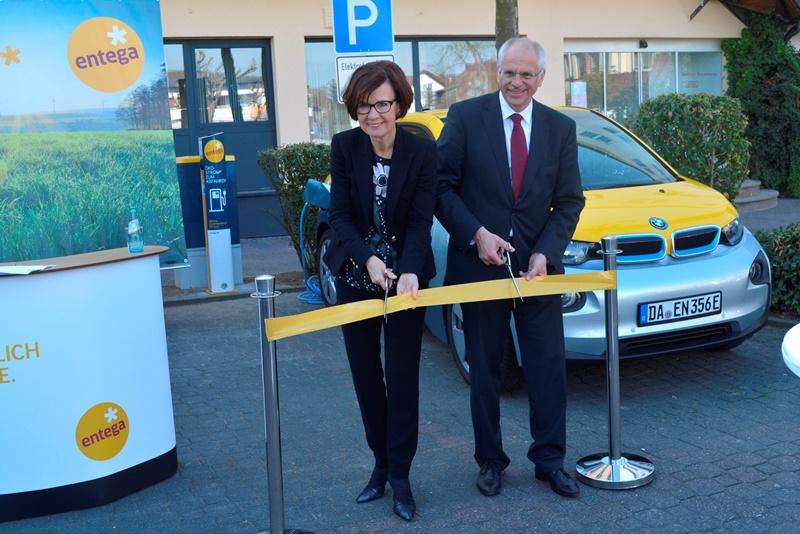 Das Foto zeigt Bürgermeister Gerald Frank und ENTEGA-Vorsitzende Marie-Luise Wolff-Hertwig beim Durchschneiden eines Bandes zur symbolischen Inbetriebnahme der E-Tankstelle auf dem Rathausplatz.