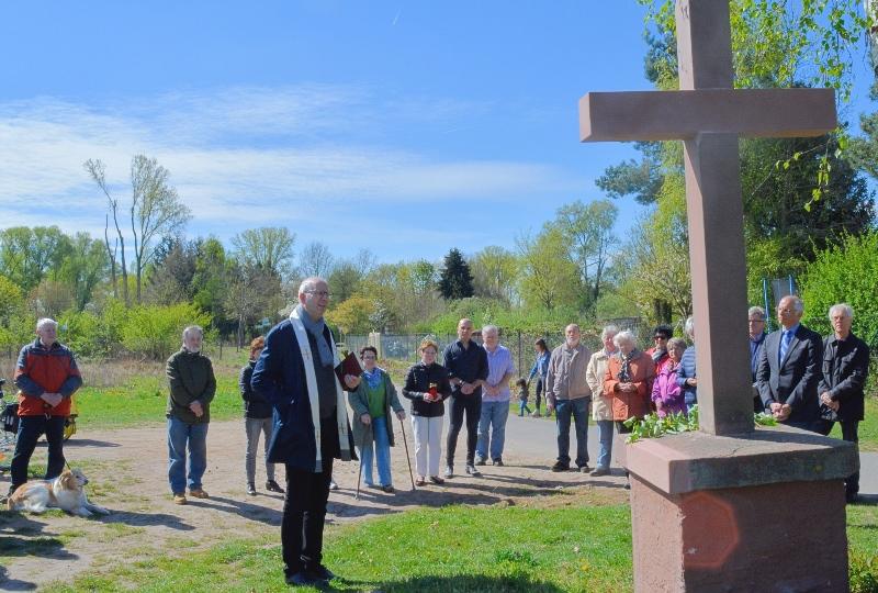 Das Foto zeigt Pfarrer Bernhard Schüpke bei der Segnung des Feldkreuzes, im Hintergrund Bürgermeister Gerald Frank und interessierte Bürger.