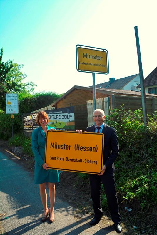 Bürgermeister Gerald Frank und die Landtagsabgeordnete Heike Hofmann präsentieren das neue Ortsschild mit der Aufschrift Münster (Hessen).