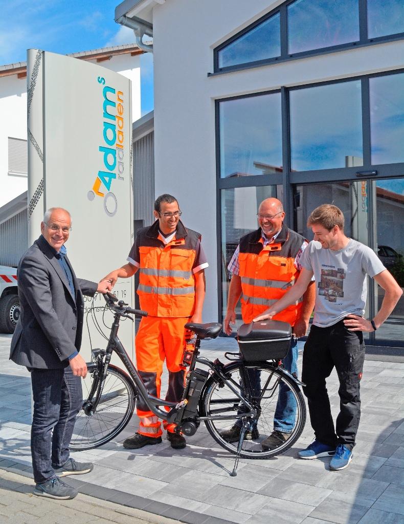 Bürgermeister Gerald Frank, Ahmed El Makhtari, Kilian Huther und Adam Schneider mit dem neuen E-Bike für die Kläranlage.