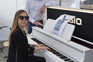 Pianistin Natalia Posnova spielt Bürgermeister Gerald Frank am Stand des Musikhauses Groh etwas vor.
