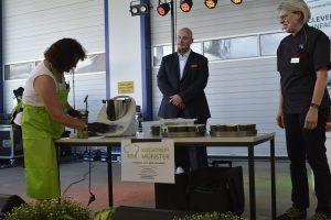 Olaf Burmeister-Salg, Abteilungsleiter Wirtschaftsförderung der Gemeinde Münster, schaut dem Team vom Kochtreff Münster bei der Kochshow über die Schulter.