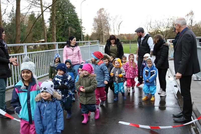 """Kurz nachdem Bürgermeister Gerald Frank das Absperrband an der neuen Brücke Nummer 8 symbolisch durchgeschnitten hat, dürfen die Kinder der neuen """"Kita an der Gersprenz"""" den Neubau erstmals betreten. Foto: GM/mmr"""