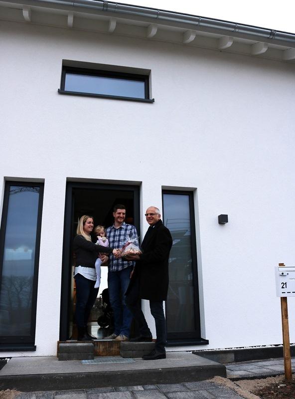 Bürgermeister Gerald Frank begrüßt die erste Familie im Neubaugebiet Im Seerich.