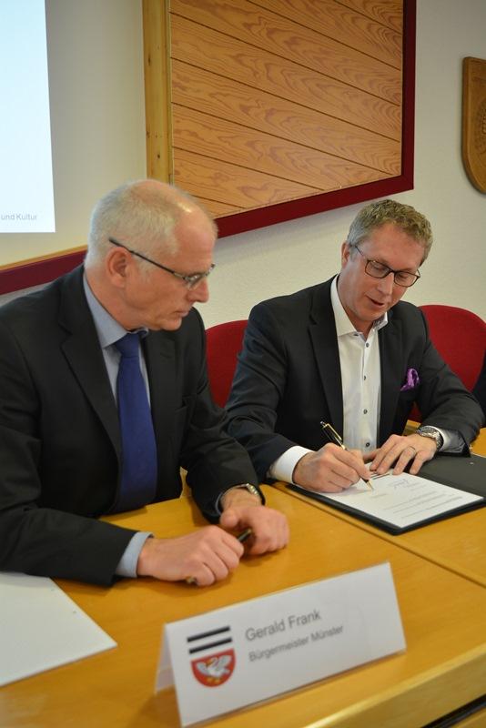 Die Bürgermeister von Münster und Messel, Gerlad Frank und Andreas Larem, unterzeichnen die Kooperationsvereinbarung im Bereich Kläranlagen. Foto: GM/MMR