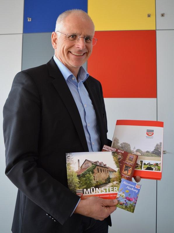"""Bürgermeister Gerald Frank präsentiert das Willkommenspaket für Neubürger, das neben vielen Info-Flyern auch ein Päckchen der """"Münsterer Mischung"""" enthält. Foto: GM/MMR"""
