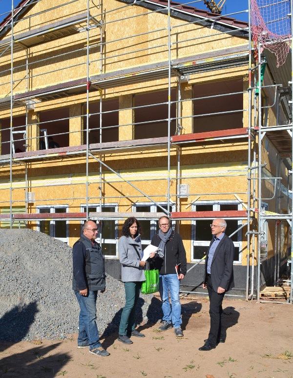 """Bürgermeister Gerald Frank (rechts) konnte sich an der Baustelle neben der """"Kinderinsel"""" gemeinsam mit Gioia Meyer von der Bauverwaltung der Gemeinde Münster und Vertretern der Firma """"KIP Fertigbau"""" ein Bild vom Baufortschritt machen. Foto: GM"""