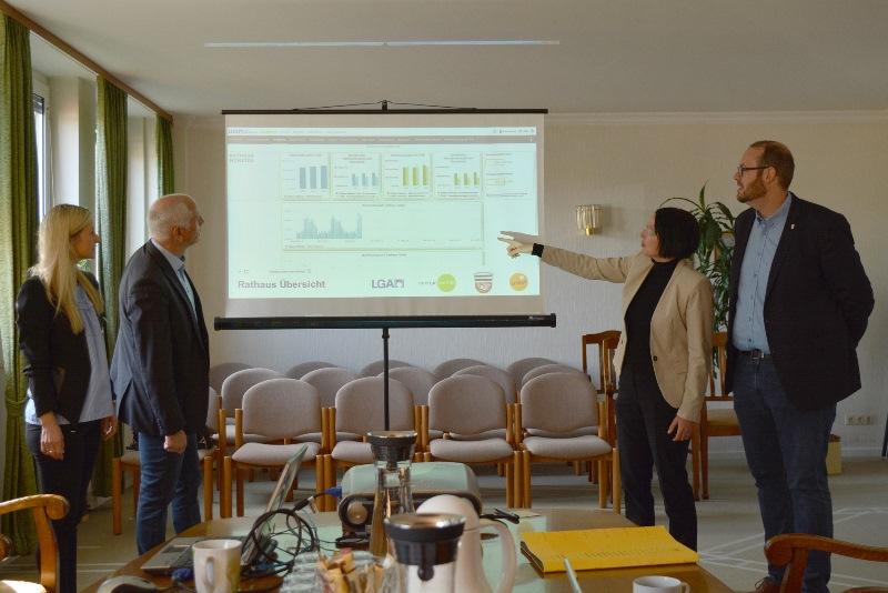ENTEGA-Regionalmanagerin Stefanie Horchler (links) und Damaris Schäfer von der Energiewende GmbH ziehen gemeinsam mit Bürgermeister Gerald Frank (links) und Klimaschutzmanager Eric Maercker eine Zwischenbilanz des Pilotprojekts für ein intelligentes, digitales Energiemanagement in der Gemeinde Münster. Foto: GM/Meike Mittmeyer-Riehl
