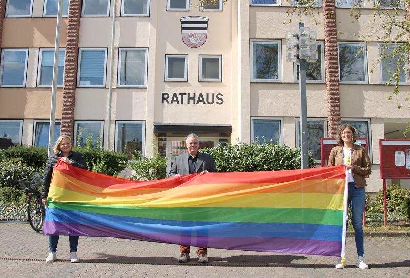 Kristina Löbig, Bürgermeister Joachim Schledt und Tamara Wolf (v.l.) präsentieren die große Regenbogenflagge, die am 17. Mai vor dem Münsterer Rathaus gehisst und eine Woche lang wehen wird. Foto: GM/Mittmeyer-Riehl